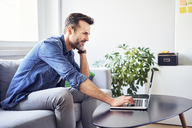 Smiling man sitting on sofa using laptop - BSZF00279