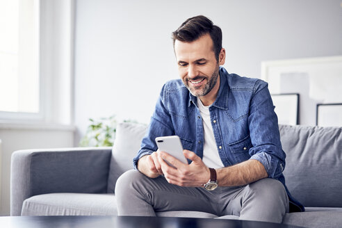 Smiling man sitting on sofa using cell phone - BSZF00291