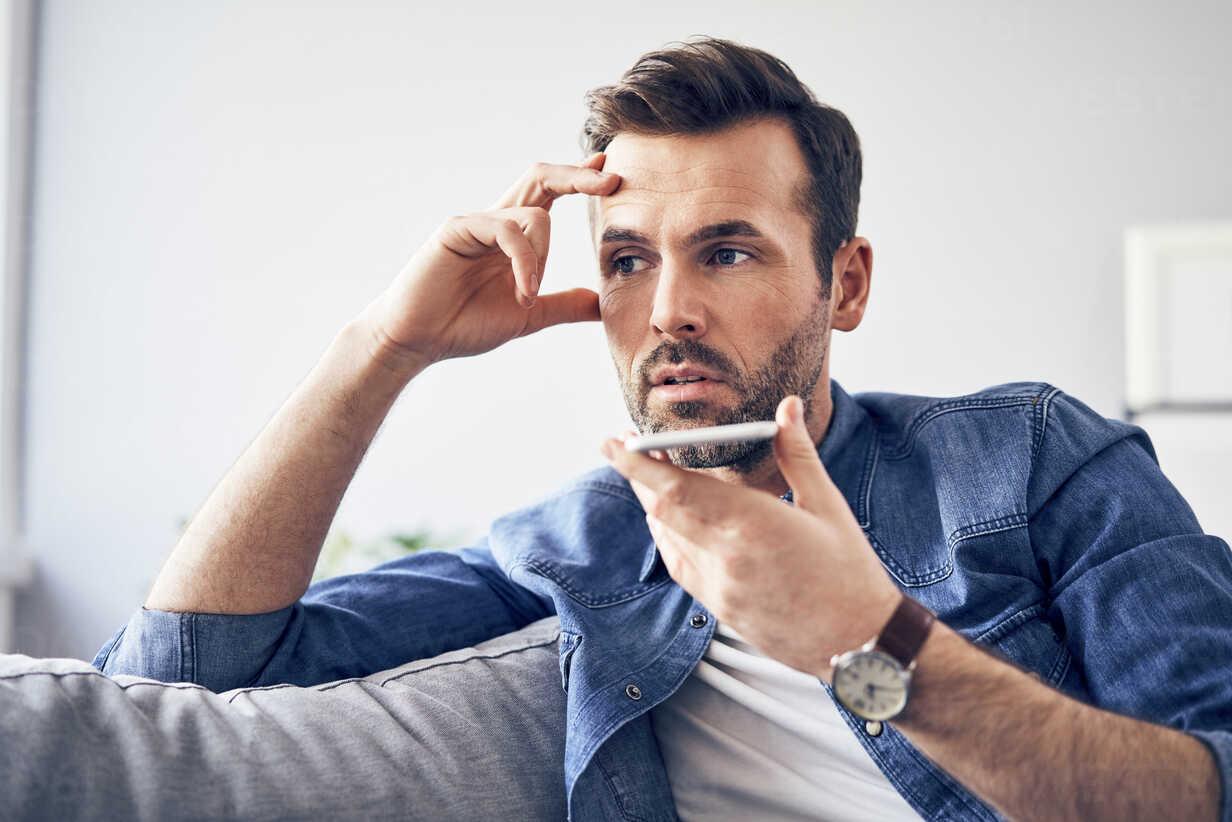 Worried man sitting on sofa using cell phone - BSZF00294 - Bartek Szewczyk/Westend61
