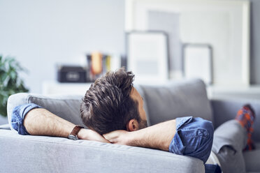 Relaxed man lying on sofa - BSZF00297