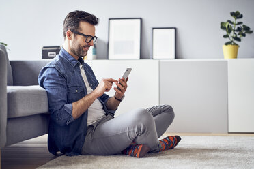 Smiling man sitting on floor in living room using cell phone - BSZF00300