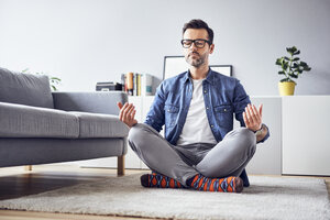 Relaxed man meditating at home - BSZF00303