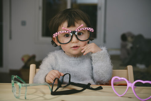 Portrait of baby girl playing with toy glasses - GEMF01898