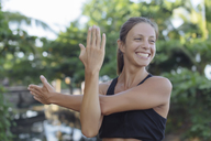 Indonesia, Bali, woman stretching arm and shoulder - KNTF01076