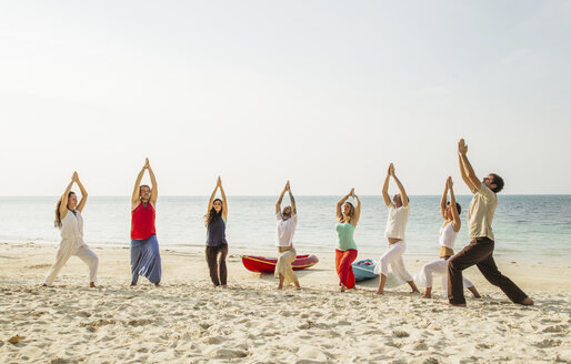 Thailand, Koh Phangan, group of people doing yoga on a beach - MOMF00384
