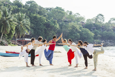 Thailand, Koh Phangan, group of people doing yoga on a beach - MOMF00387