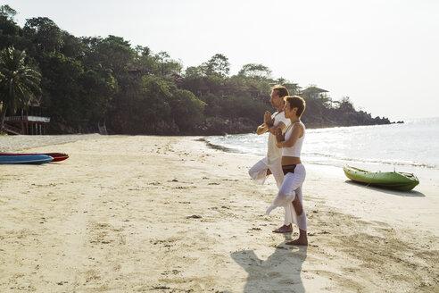 Thailand, Koh Phangan, couple doing yoga on a beach - MOMF00390