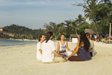 Thailand, Koh Phangan, group of people meditating together on a beach - MOMF00393