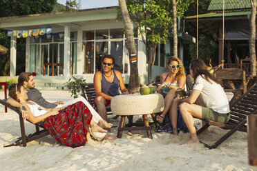 Thailand, Koh Phangan, friends having fun in a cafe at the beach - MOMF00399