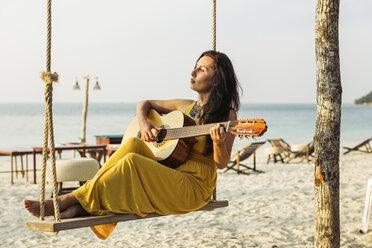 Thailand, Koh Phangan, woman playing guitar at the beach - MOMF00402