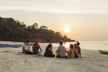 Thailand, Koh Phangan, group of people sitting on a beach with guitar at sunset - MOMF00405