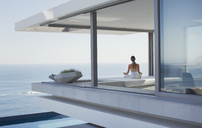 Serene woman meditating on modern, luxury home showcase exterior patio with ocean view - HOXF01027