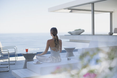 Serene woman meditating on modern, luxury home showcase exterior patio with ocean view - HOXF01030