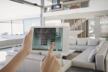 Personal perspective woman with digital tablet managing digital security system in modern, luxury home showcase interior living room - HOXF01039