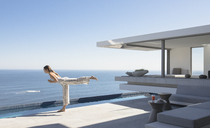Woman practicing yoga warrior 3 pose on sunny modern, luxury home showcase exterior patio with ocean view - HOXF01042