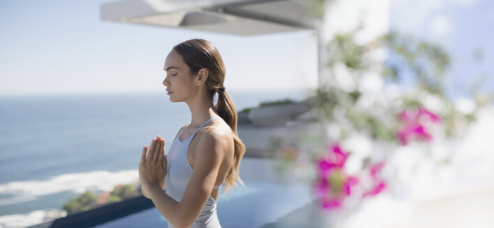 Serene brunette woman practicing yoga, meditating with hands at heart center on sunny patio with ocean view - HOXF01051