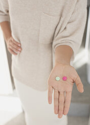 Woman holding, showing two pills, pink and green - HOXF01054