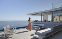 Woman in dress walking on sunny, modern, luxury home showcase exterior patio with ocean view - HOXF01060