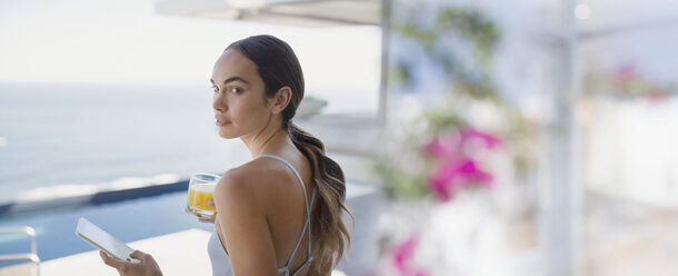 Brunette woman drinking orange juice and using digital tablet on luxury patio - HOXF01063