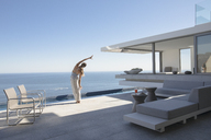 Woman practicing yoga side stretch on modern, luxury home showcase exterior patio with sunny ocean view - HOXF01066