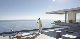 Woman walking on sunny, modern, luxury home showcase exterior patio with ocean view - HOXF01069