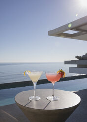Cocktails in martini glasses on sunny luxury patio with ocean view - HOXF01078