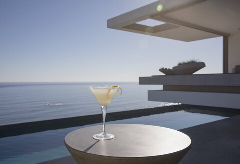 Lemon cocktail in martini glass on sunny luxury patio with ocean view - HOXF01084