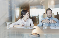 Businesswoman listening to businessman in conference room meeting - HOXF01138