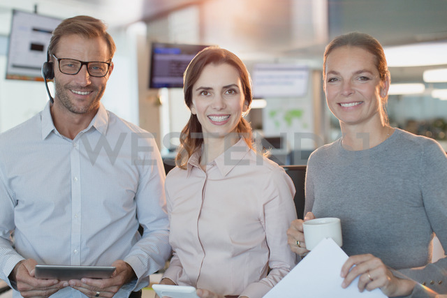 Portrait smiling, confident business people with digital tablet and coffee in office - HOXF01144
