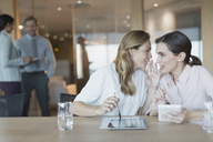 Businesswomen with digital tablets whispering in conference room meeting - HOXF01153