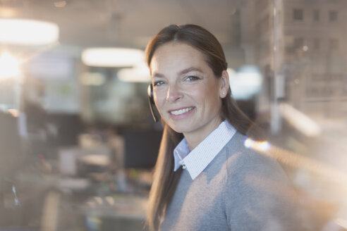 Portrait smiling, confident businesswoman wearing headset in office - HOXF01189
