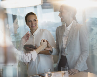Businesswomen laughing, handshaking in office meeting - HOXF01213