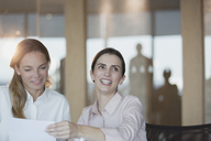 Smiling, enthusiastic businesswoman in conference room meeting - HOXF01219