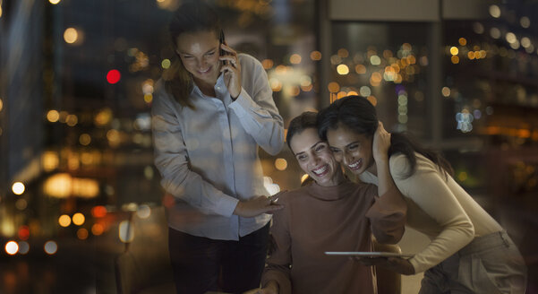 Happy businesswomen celebrating, working late in office at night - HOXF01234