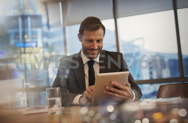 Smiling businessman using digital tablet in conference room - HOXF01237