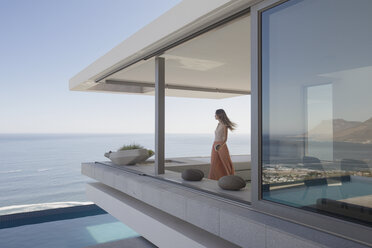 Woman looking at ocean view on modern, luxury home showcase exterior balcony - HOXF01249