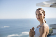 Portrait serene woman practicing yoga with hands at heart center on sunny patio with ocean view - HOXF01255