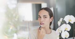 Portrait brunette woman applying lipstick - HOXF01261