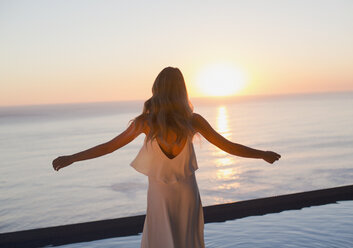Woman with arms outstretched watching tranquil sunset view over ocean horizon - HOXF01264