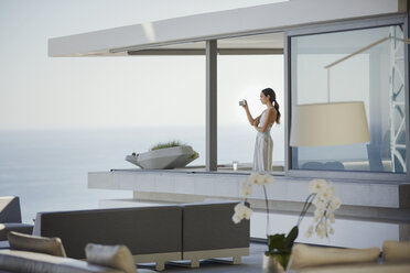 Woman with digital camera photographing ocean view on modern, luxury home showcase balcony - HOXF01267