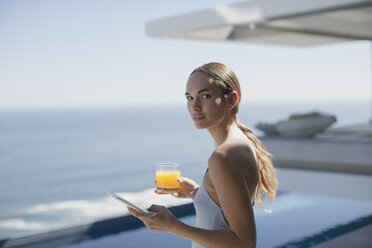 Portrait woman using digital tablet and drinking orange juice on sunny luxury patio with ocean view - HOXF01270