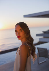 Portrait serious, beautiful woman on sunset patio with ocean view - HOXF01273
