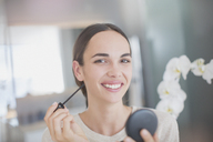 Portrait smiling, confident woman applying mascara with mascara wand and compact mirror - HOXF01276