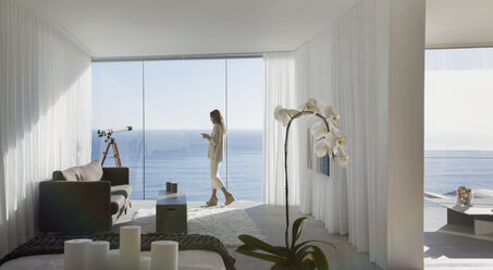 Woman standing on modern luxury home showcase balcony with sunny ocean view - HOXF01279