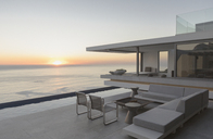 View of sunset over ocean horizon from modern, luxury home showcase exterior patio - HOXF01291