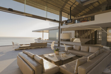 Sunny modern, luxury home showcase interior living room open to ocean view - HOXF01297