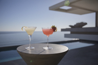 Cocktails in martini glasses on sunny luxury patio with sunny ocean view - HOXF01315