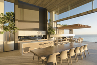 Sunny modern, luxury home showcase interior dining table with ocean view - HOXF01321