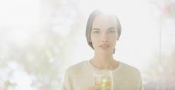 Portrait confident, serious brunette woman drinking juice - HOXF01324