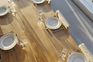 Placesettings on sunny wooden patio table - HOXF01333